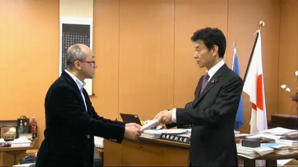 西村康稔内閣府副大臣に「TPP著作権条項に関する緊急声明案」を手渡した