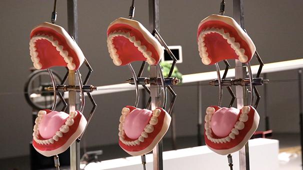 立体機動装置で飛んだスマホ目掛けて、巨人の口に見立てた入れ歯が閉じていくギミック