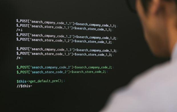 残業中PHPコードを書くシステムエンジニア(モデル:大川竜弥)